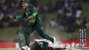 Pakistan's Umar Akmal (L) celebrates after running out Kenya's Seren Waters during their ICC Cricket World Cup group A match in Hambantota, south of Colombo, 23 February 2011