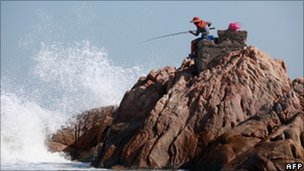 File image of a fisherman on a rocky outcrop in Hong Kong on 31 October 2010