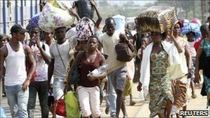 Residents flee with their belongings after clashes between forces loyal to incumbent President Laurent Gbagbo and his rival Alassane Ouattara in Abobo, in Abidjan, 25 February 2011