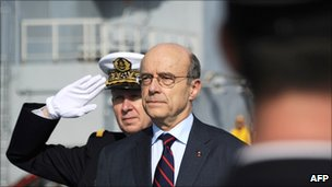 Alain Juppe reviews the troops onboard the Mistral high-tech amphibious helicopter carrier assault and command ship on 18 February 2011