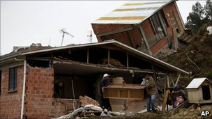 People recover furniture from a ruined home after a landslide in La Paz, Bolivia