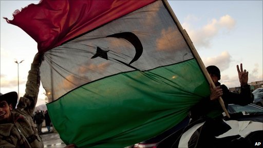Libyans hold the former royal flag as they drive past a demonstration against Libyan leader Muammar Gaddafi in Benghazi, 27 February 2011
