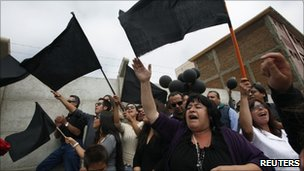 People in the Chilean town of Constitucion wave black flags in protest at government reconstruction efforts after the earthquake and tsunami of 27 February 2010