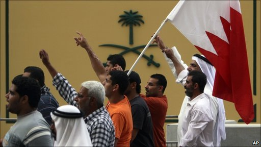 Bahraini anti-government protesters wave the national flag as they march past the embassy of Saudi Arabia in the capital Manama, 27 February 2011