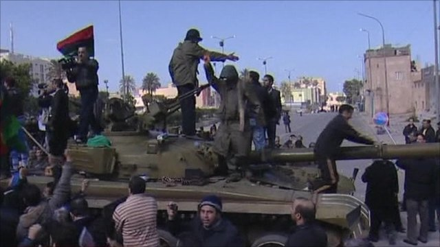 Protesters climb on tank