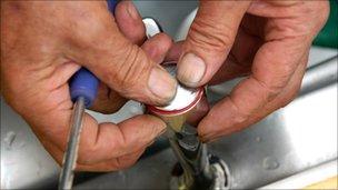 Plumber fixes a tap