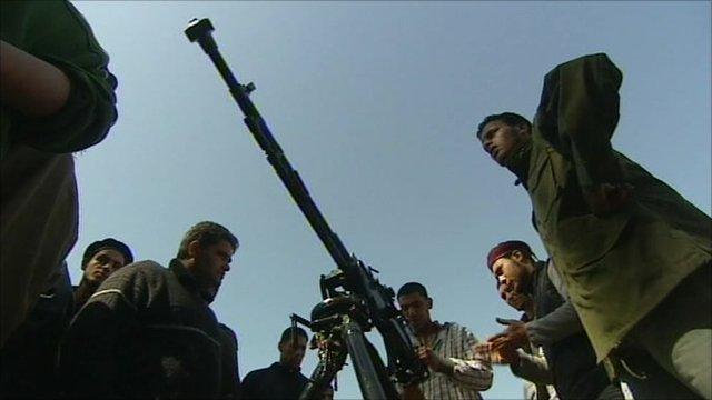 Men gathered around a weapon