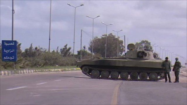 Military troops stand by tank on road into Zawiya