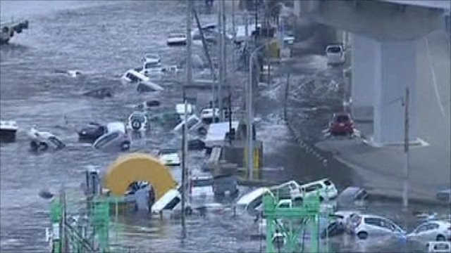 A wave surge sweeps away cars in Japan