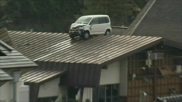 A car is perched on top of a building