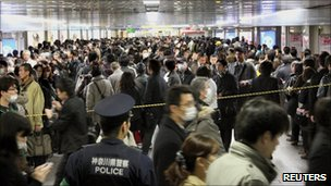Commuters stand in line to board other trains at Yokohama Station, southwest of Tokyo