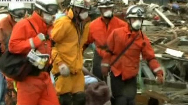 Rescue workers bring out survivor on stretcher