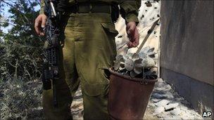 Israeli soldier gathers mortars fired on Saturday