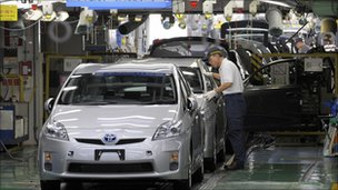 Factory worker checking an assembled Prius