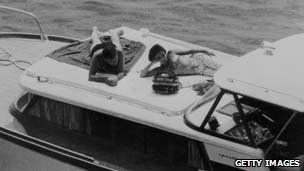 Actors Elizabeth Taylor and Richard Burton recline on the deck of a speedboat during a holiday in Ischia, June 1962