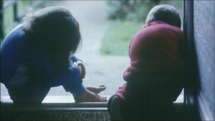 Young girl and boy sat in doorway