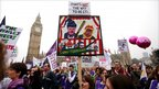Protesters marching past Big Ben with a sign depicting David Cameron and Nick Clegg as the characters Punch and Judy