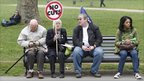 Four protesters sit peacefully on a park bench