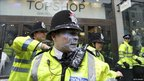 A policeman outside Topshop Oxford Circus with grey paint splashed on his face and uniform