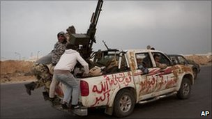 Libyan rebels jump onto the back of their vehicle as they leave Ras Lanuf. Photo: 29 March 2011