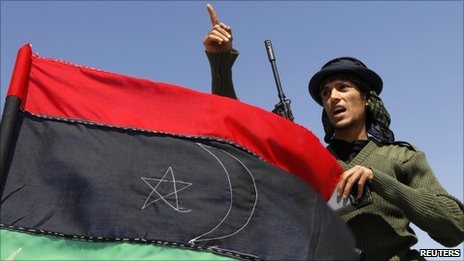 A rebel fighter gestures beside a Kingdom of Libya flag