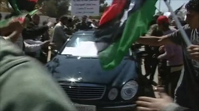 Car surrounded by demonstrators