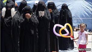 Yemeni women protesters pray in Sanaa, 12 April