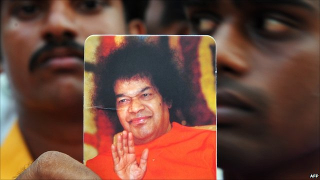 Man holding picture of Sri Satya Sai Baba