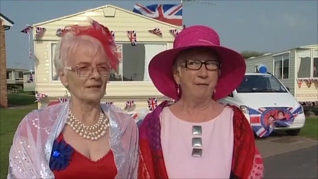 Two women in front of a decorated caravan