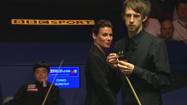 Judd Trump is watched by Ding Junhui & referee Michaela Tabb