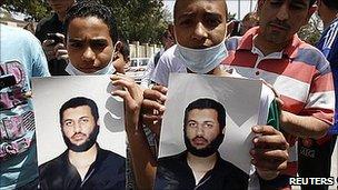 Pro-Gaddafi supporters hold pictures of Saif al-Arab Gaddafi. 1 May 2011