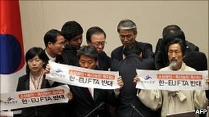 """Lawmakers from South Korea's opposition Democratic Labor Party hold banners reading """"No to Korea-EU FTA"""""""