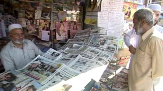 Men standing at a newspaper stall in Abbottabad