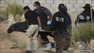 Forensic workers carry the bodies of four men, as federal polices stand guard at a crime scene on the outskirts of Ciudad Juarez, 13 April 2011