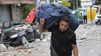 A man carries a bag down an earthquake-damaged street in Lorca, Spain - 12 May 2011