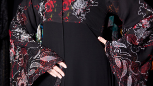 A red and black abaya with flowers patterns and lace