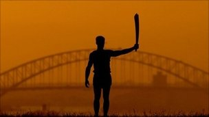 The 2000 Sydney Olympic Games torch silhouetted against Sydney Harbour Bridge