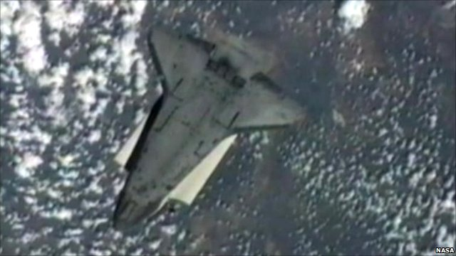 Space shuttle Endeavour mid-back-flip over Earth