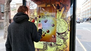 A man plays with one of JCDecaux's interactive bus shelter displays