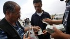Palestinian travellers exchange currency before crossing into Egypt