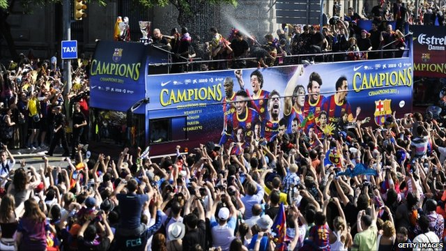 Barcelona players celebrate on board an open top bus after winning the UEFA Champions League Final