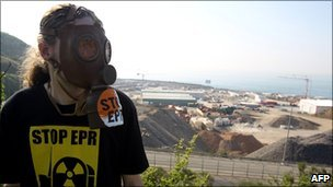 A protester wearing a gas mask stands in front of the construction site of the third-generation European Pressurised Water nuclear reactor (EPR) in Flamanville, during an anti-nuclear demonstration, on 23 April, 2011