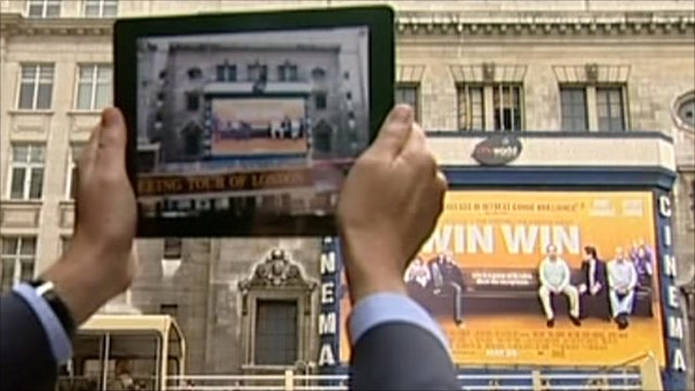 Tablet computer held up to film poster