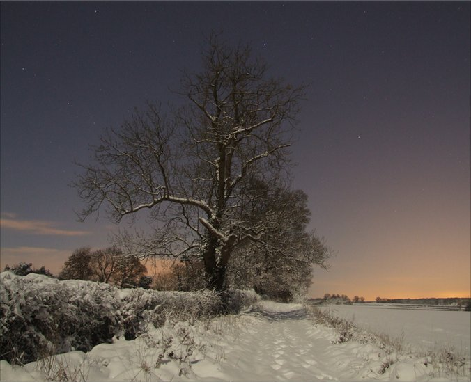A full moon on a clear night illuminates the heavy snowfall in Oxfordshire, UK