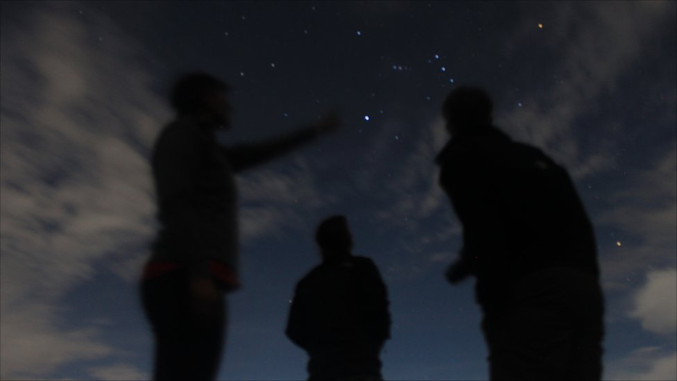 Figures standing and pointing at stars in the sky