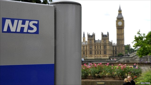 """NHS sign in the grounds of St Thomas"""" Hospital, in front of the Houses of Parliament"""