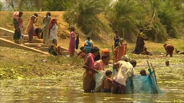 People wash clothes in a lake