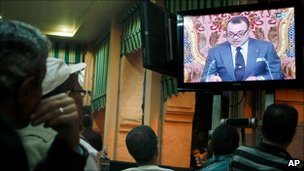 Moroccan customers watch a live broadcast from Rabat of a speech by Morocco's King Mohammed VI at a cafe in Casablanca, on 17 June 2011
