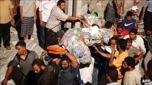 In a picture taken on a government-guided tour, people carry the body of a young man from the rubble of what Libyan authorities say was a Nato air strike in Tripoli, 19 June 2011