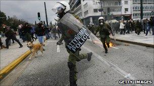 A Greek riot police officer running